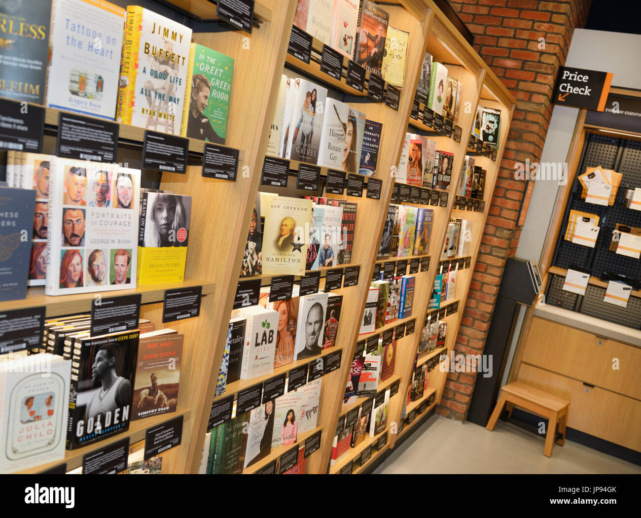 Rows of books in an Amazon Books retail store with a screen to scan for a price check - Stock Image