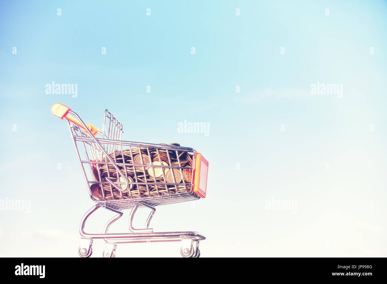 Miniature supermarket shopping cart filled with golden coins against blue sky, color toning applied. - Stock Image