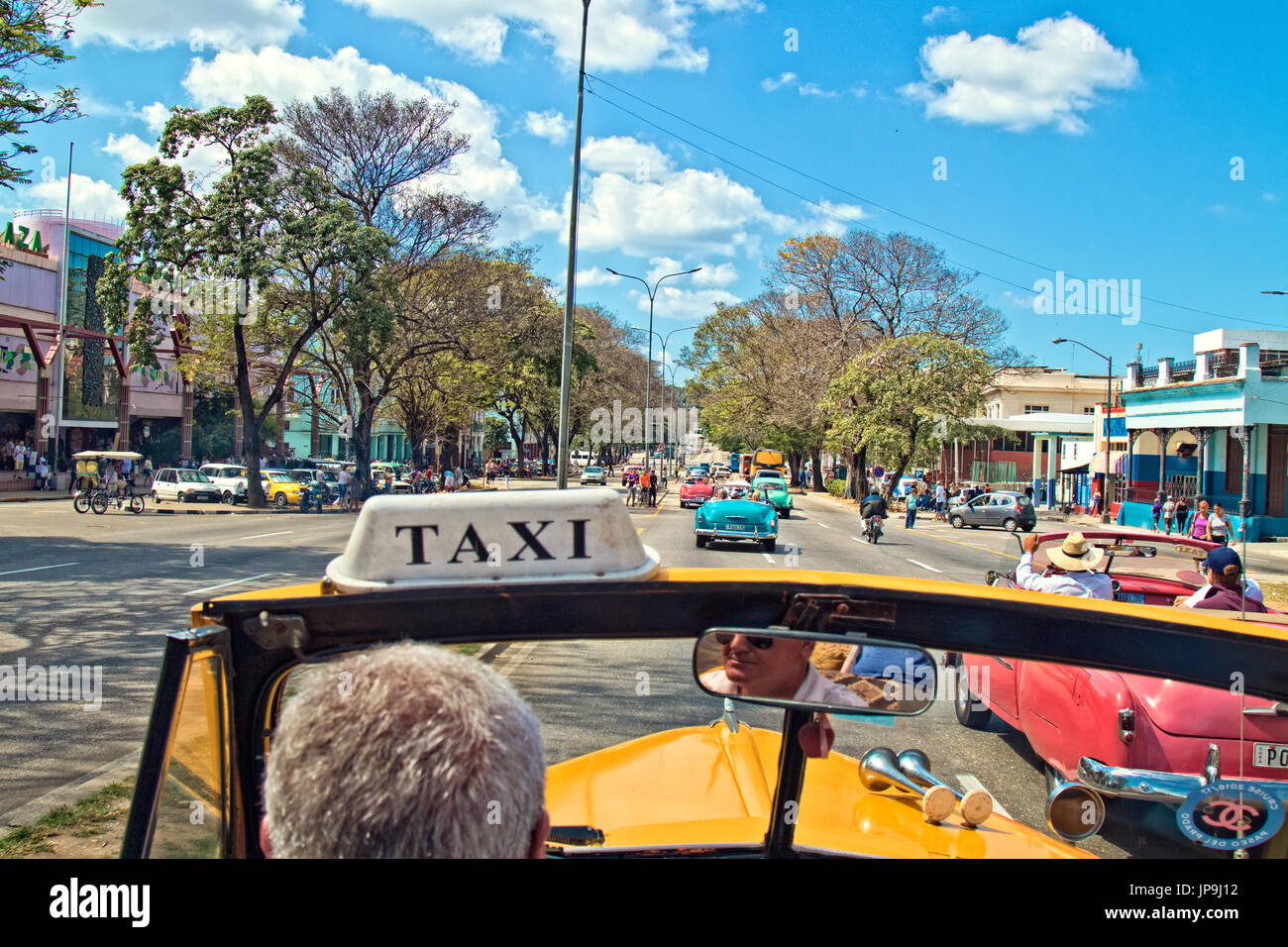 Convertible taxicab driving through the streets of Havana, Cuba. - Stock Image