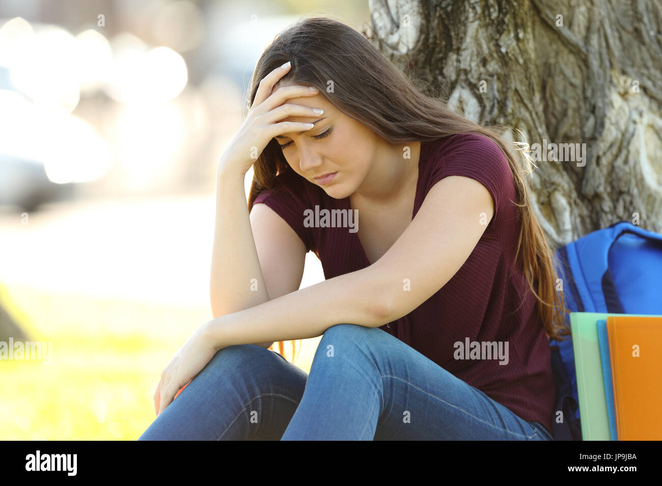 Single concerned student lamenting alone outdoors in a park - Stock Image