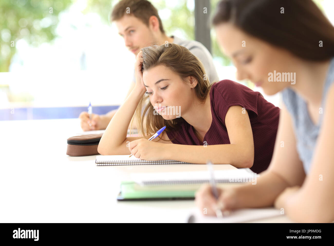 Uninterested student drawing during a class in a classroom - Stock Image