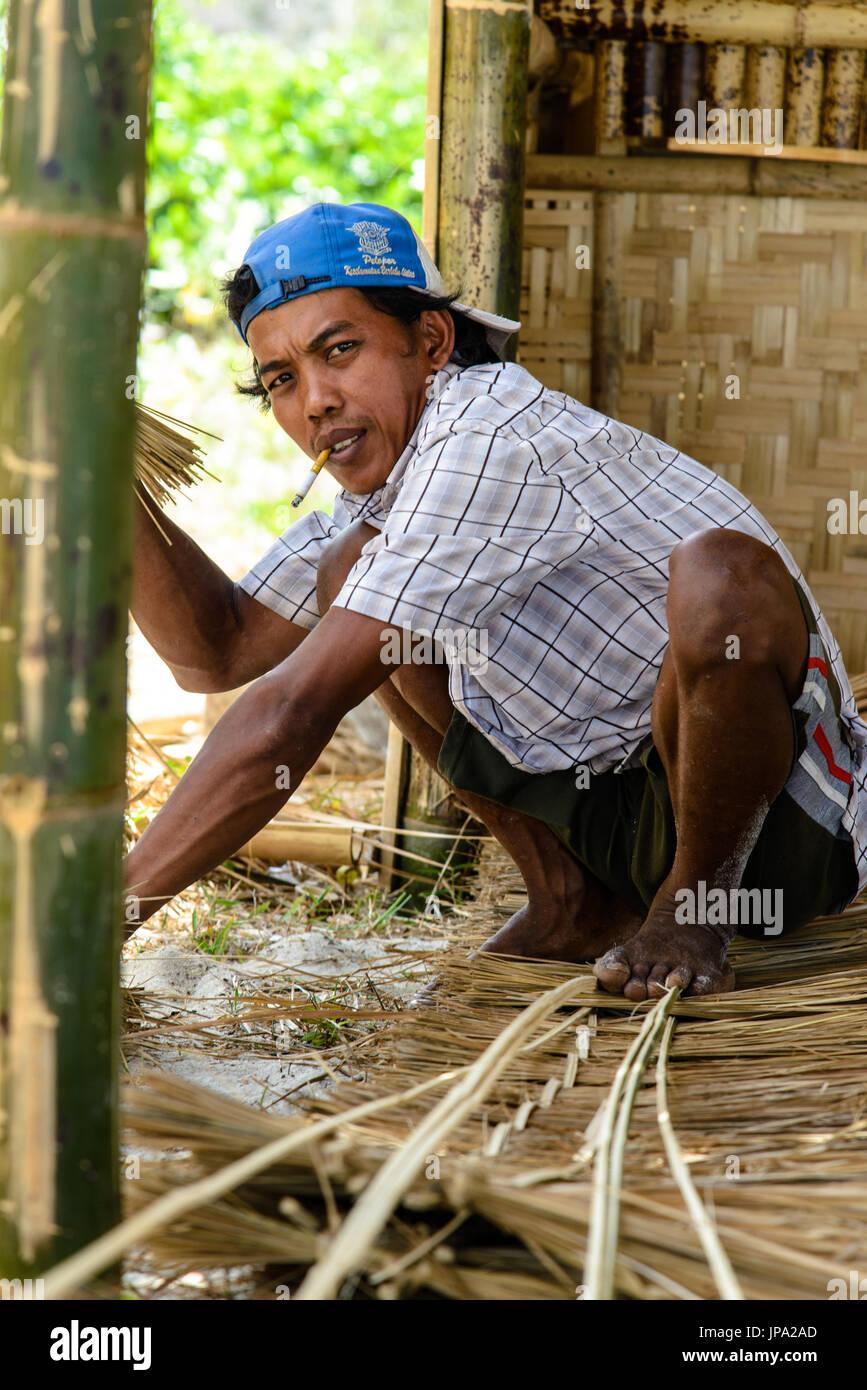 SELONG BELANAK BEACH, LOMBOK, INDONESIA  - SEPTEMBER 08, 2014: Indonesian constructing a bamboo hut - Stock Image