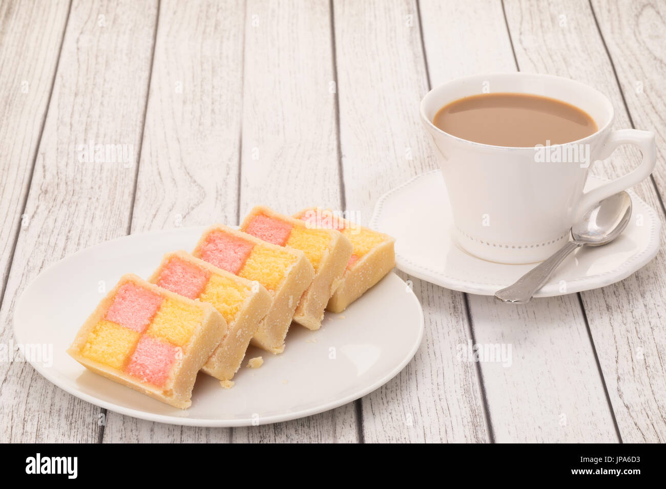Slices of Battenburg cake with a cup of coffee - Stock Image