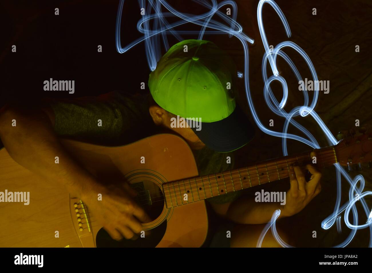 Creative photography using light painting method on a man playing the guitar. - Stock Image