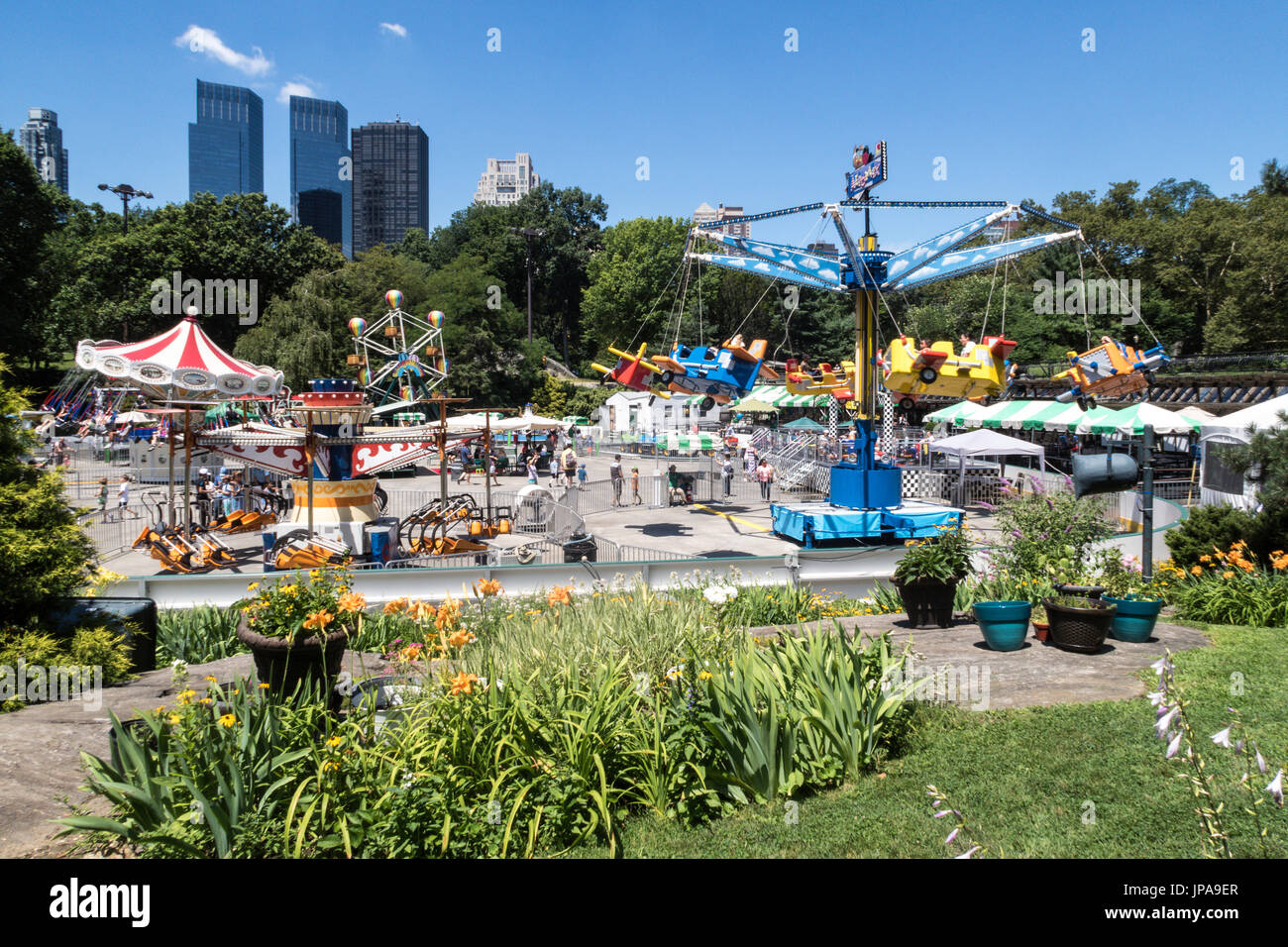 Victorian Gardens, Carnival Rides In Central Park With The Manhattan  Skyline In Background, NYC, USA