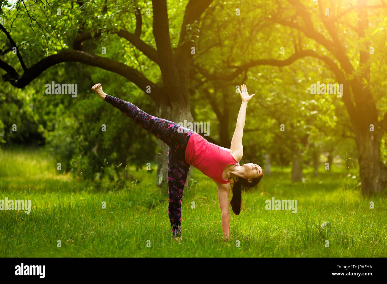 young woman standing in half moon pose, while practicing yoga. - Stock Image