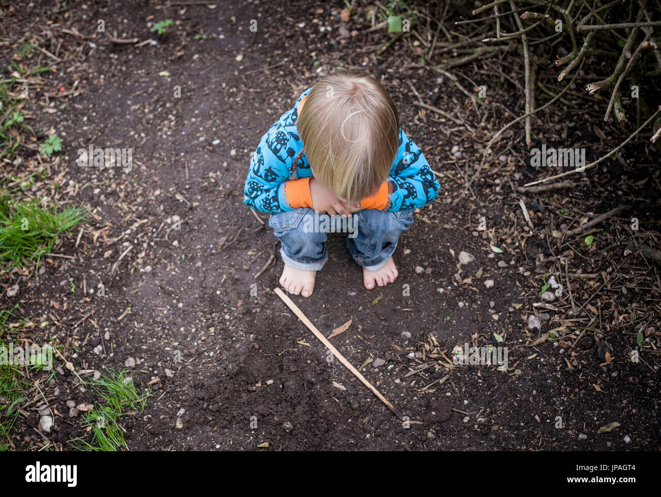 Child plays on forest floor, recorded from above - Stock Image