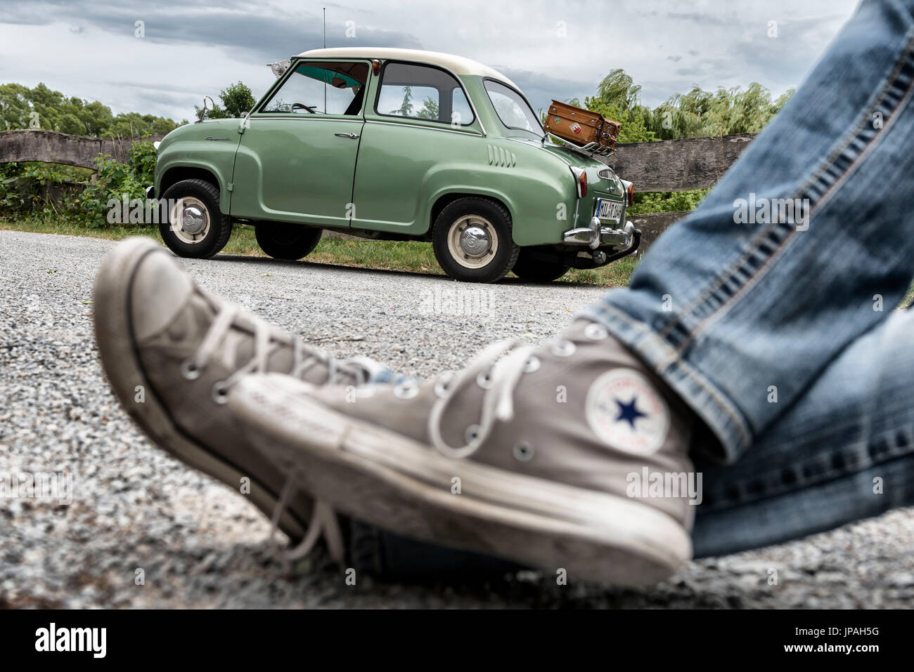 legs with sneakers in front of a Goggomobil - Stock Image