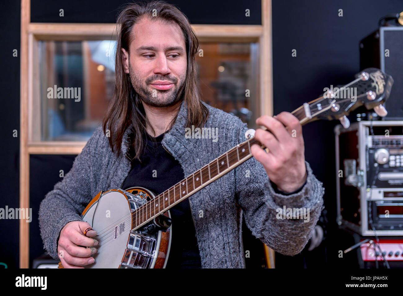 Musicians in the sound studio playing the banjo - Stock Image