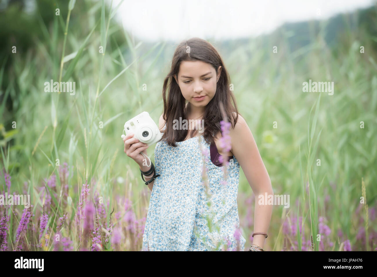 Girls with camera in high grass - Stock Image