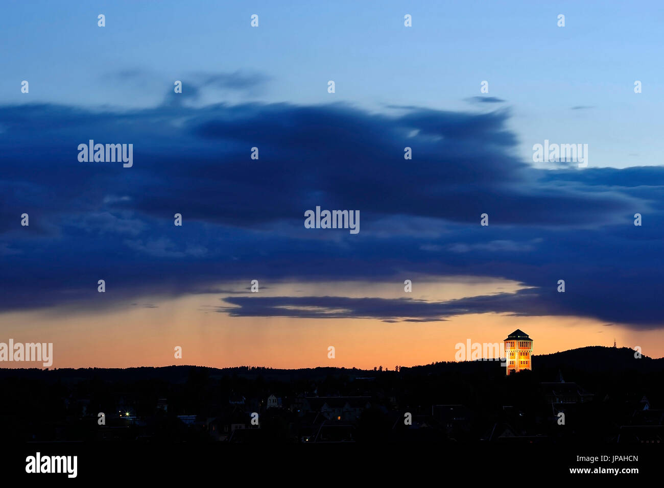 Hoist frame of the Karl-Liebknecht shaft in the Oelsnitz/Erzgebirge with rain cloud shortly after sundown - Stock Image