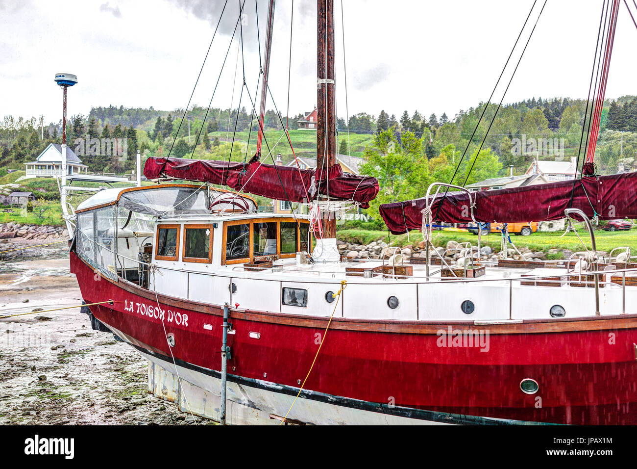 Port-au-Persil, Canada - June 2, 2017: Pier and harbor with red ship and sign La Toison D'Or in village of Quebec Stock Photo