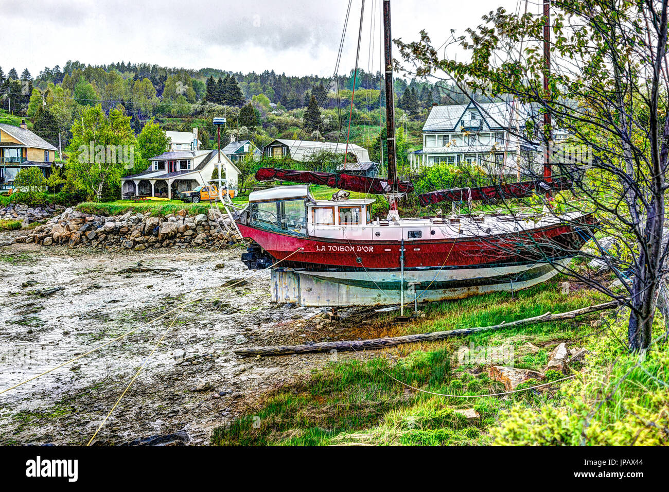 Port-au-Persil, Canada - June 2, 2017: Pier and harbor with red ship and sign La Toison D'Or in village of Quebec in Charlevoix region during stormy r - Stock Image