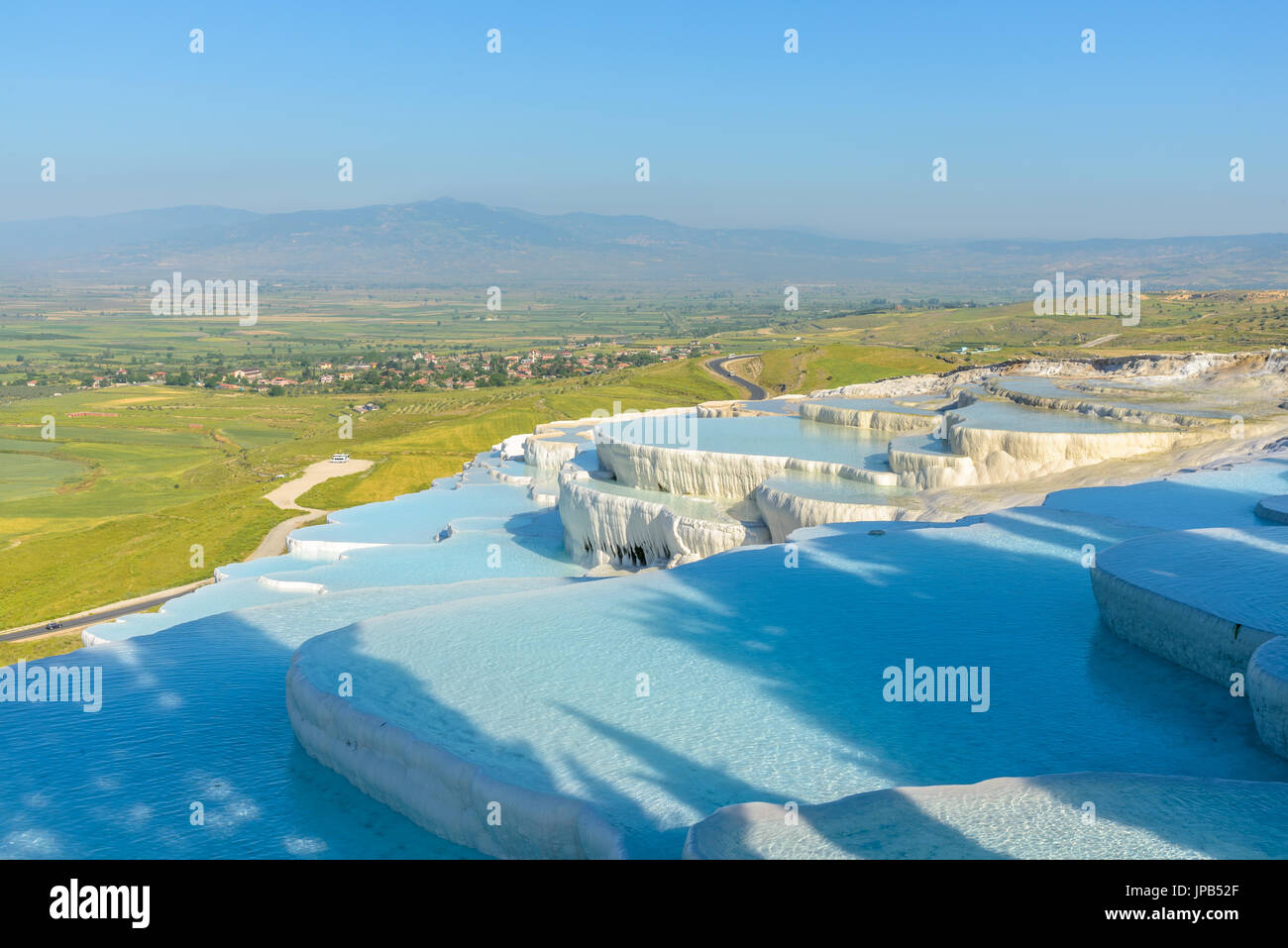 The enchanting pools of Pamukkale in Turkey. Pamukkale contains hot springs and travertines, terraces of carbonate minerals left by the flowing water. - Stock Image