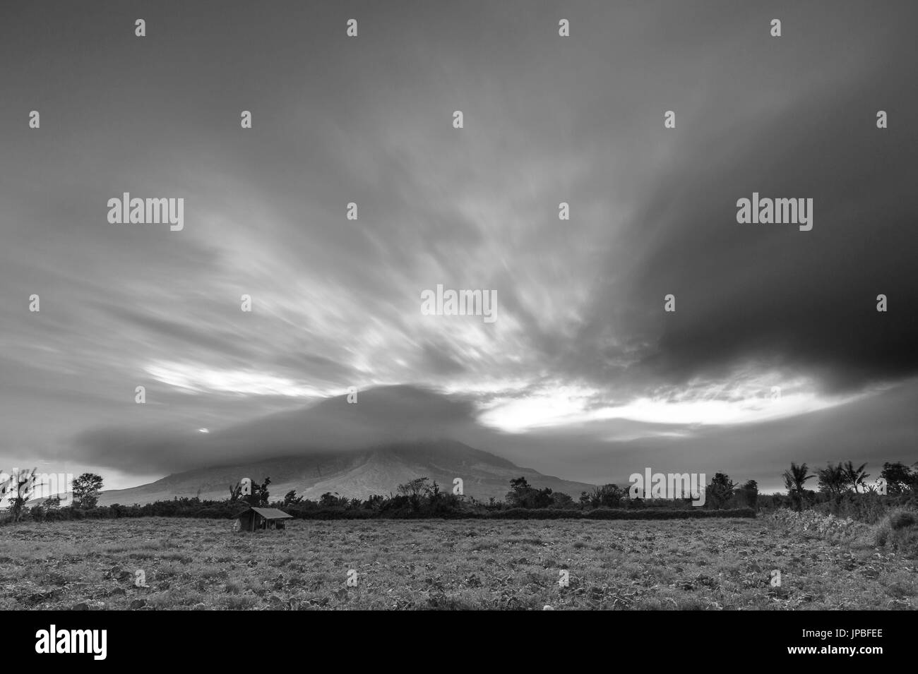 Black and white recording of the active volcano Mt. Sinabung on Sumatra, with special beautyful clouds and ash cloud during sundown. - Stock Image