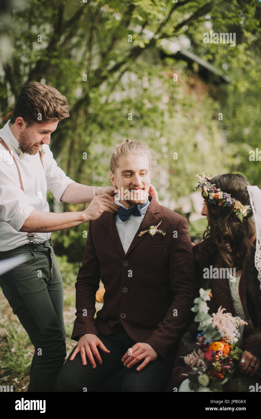 Alternate bridal couple at wedding ceremony outdoors, witness ties bridegroom the bow tie, excitement, nervousness - Stock Image