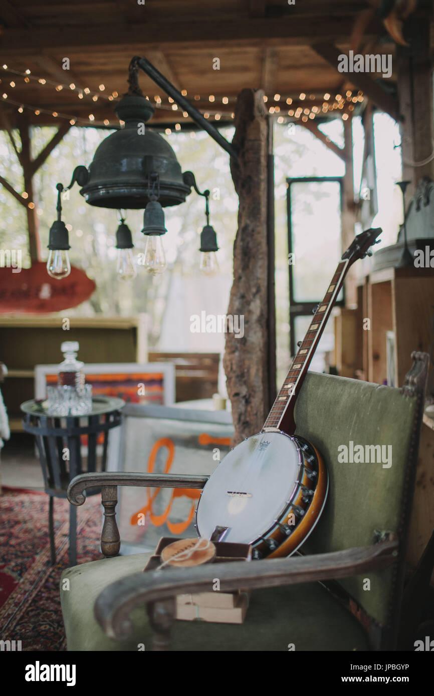 garden shed, inside, furnishing, armchair, banjo, string of lights - Stock Image