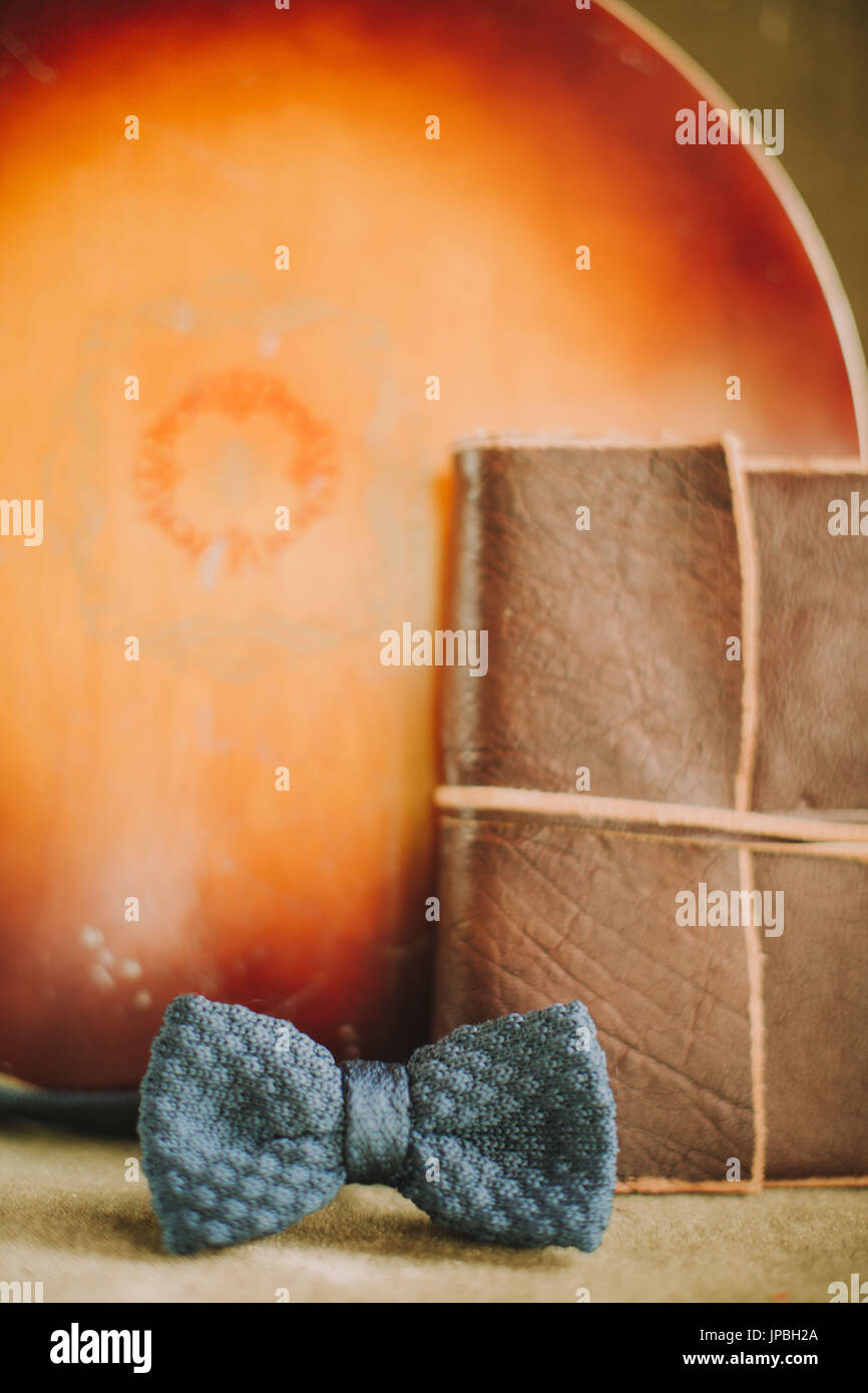 Stilllife, music instrument, book with leather binding and bow-tie - Stock Image