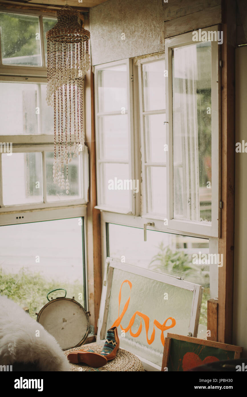 Alternative interior furnishing in a garden shed, window with the inscription 'Love' - Stock Image