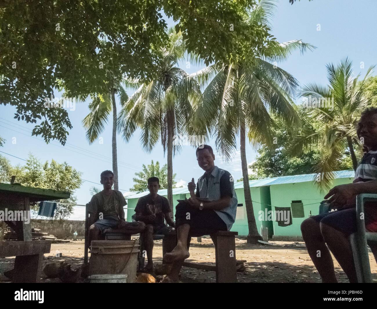 Teachers of primary school in Kampung Rinca sitting in the shadow, people, men, man, photojournalism - Stock Image