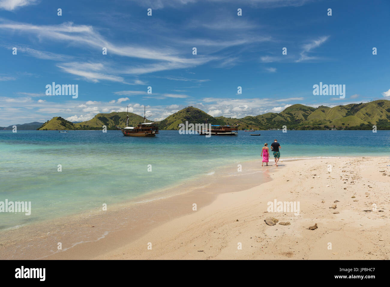 Couple walking along a beach in the Flores sea, Indonesia, Komodo, dream, holiday - Stock Image