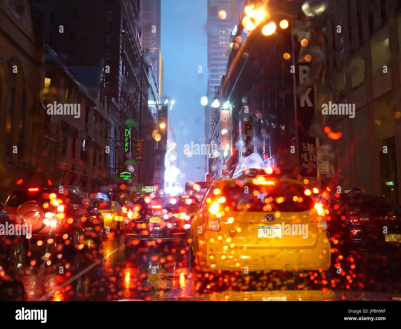 Rain drops on car's windshield are illuminated red by taxicab brake lights - Stock Image