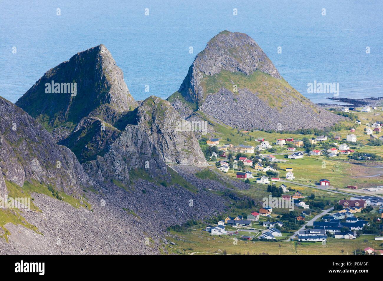 Rocky peaks frame the village of Sorland surrounded by sea Vaeroy Island Nordland county Lofoten archipelago Norway Europe - Stock Image