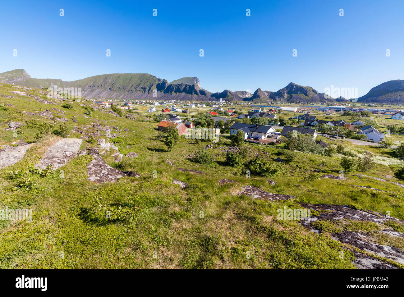 Green meadows frame the village of Sorland surrounded by sea Vaeroy Island Nordland county Lofoten archipelago Norway Europe - Stock Image