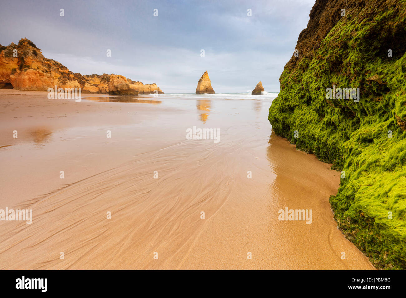 Rocks surrounding the sandy beach are reflected in the clear water Albandeira Lagoa Municipality Algarve Portugal Stock Photo