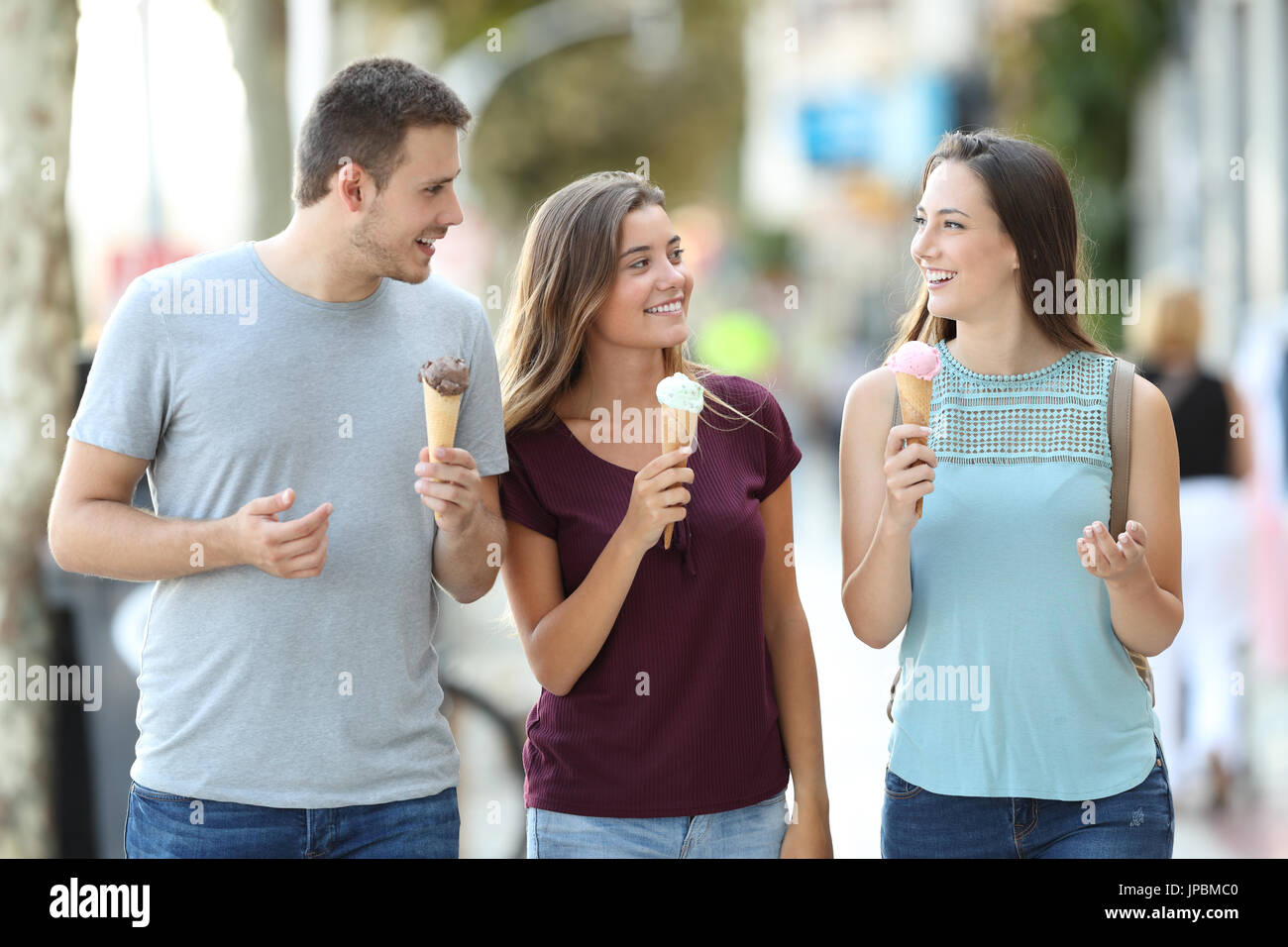 Front view of three happy friends talking and eating ice creams walking in the street Stock Photo