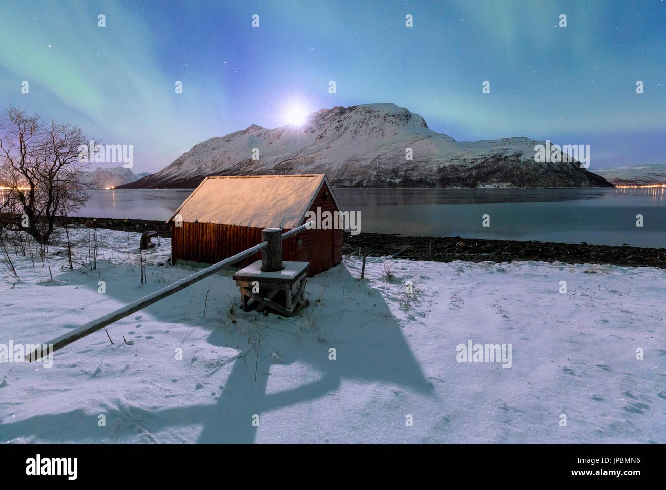 Northern lights over the fjord illuminates by the moon. Ravelseidet, Rotsundet, Lyngenfjord, Lyngen Alps, Troms, Norway, Lapland, Europe. - Stock Image