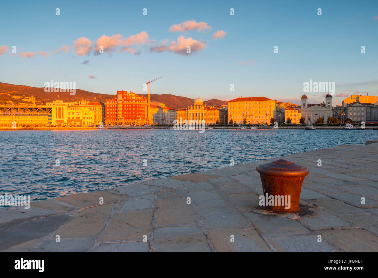 The neoclassic structures seen from Audace molo in Trieste at sunset. Trieste city, Trieste Province, Friuli Venezia Giulia district, Italy, Europe - Stock Image