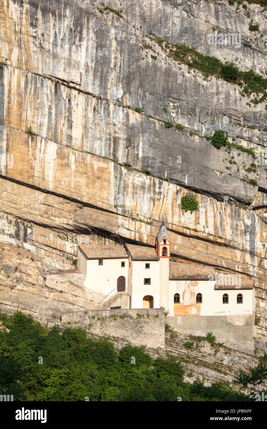 A view of Eremo di San Colombano, a monastery in Trambileno, Province of Trento, Italy, notable for its location in the side of a mountain. - Stock Image