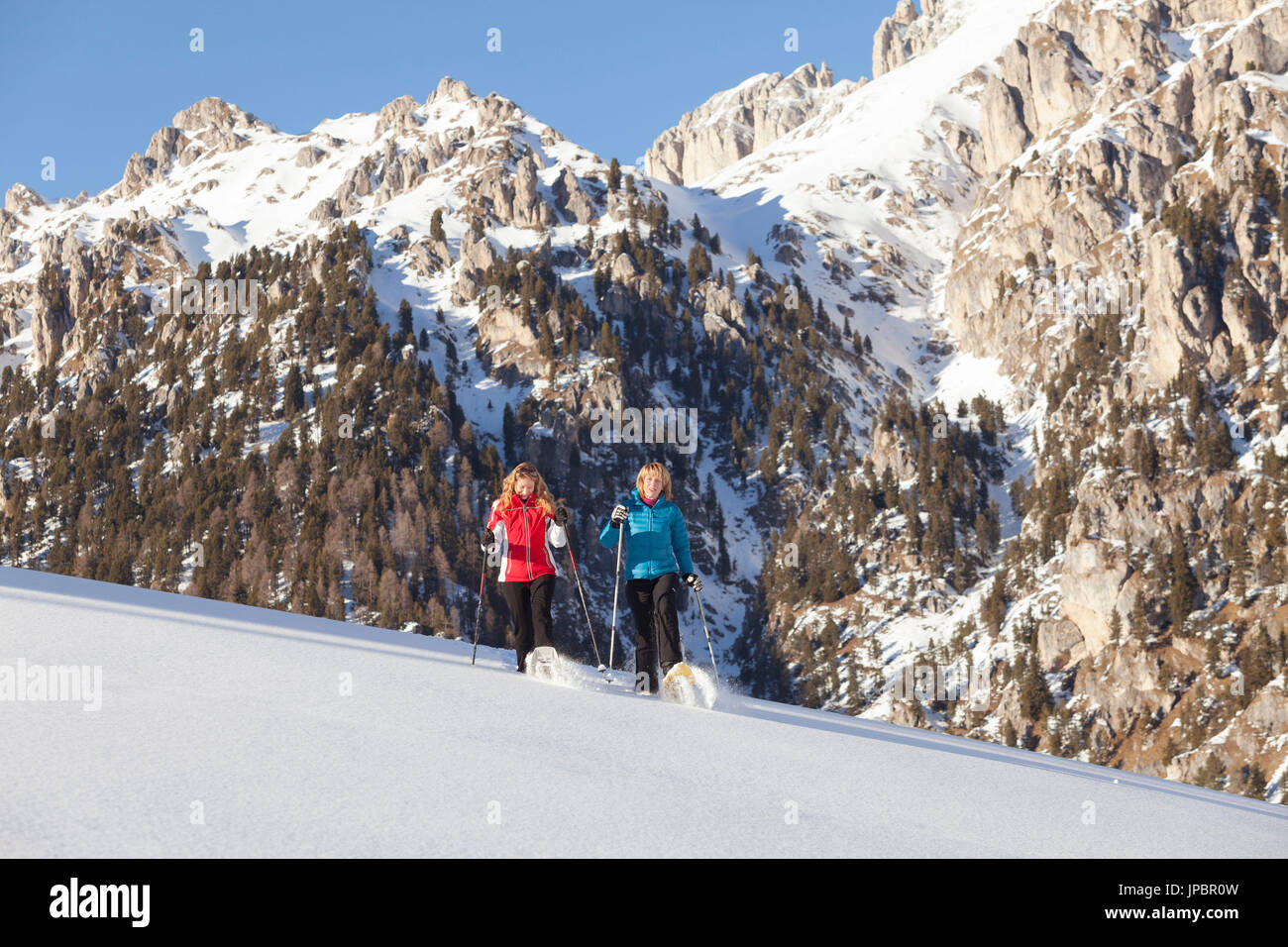 two models are walking with snowshoes on fresh snow feeling the emotion of the powder, Villnöss, Bolzano province, South Tyrol, Trentino Alto Adige, Italy, Europe - Stock Image