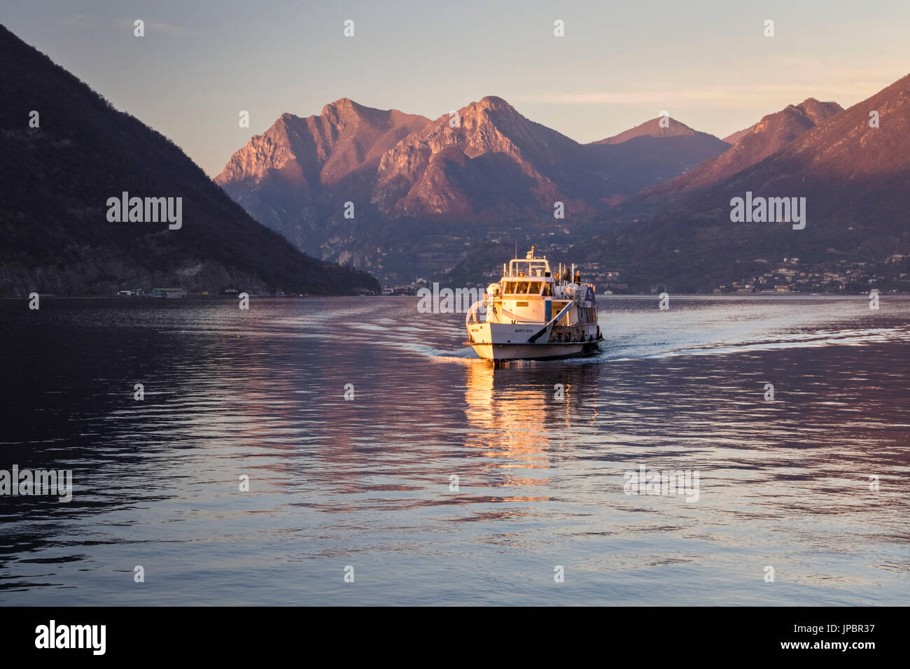 A boat approaching Sulzano, in the distance the mount Corna Trentapassi, Brescia Province, Iseo Lake, Lombardy, Italy. - Stock Image
