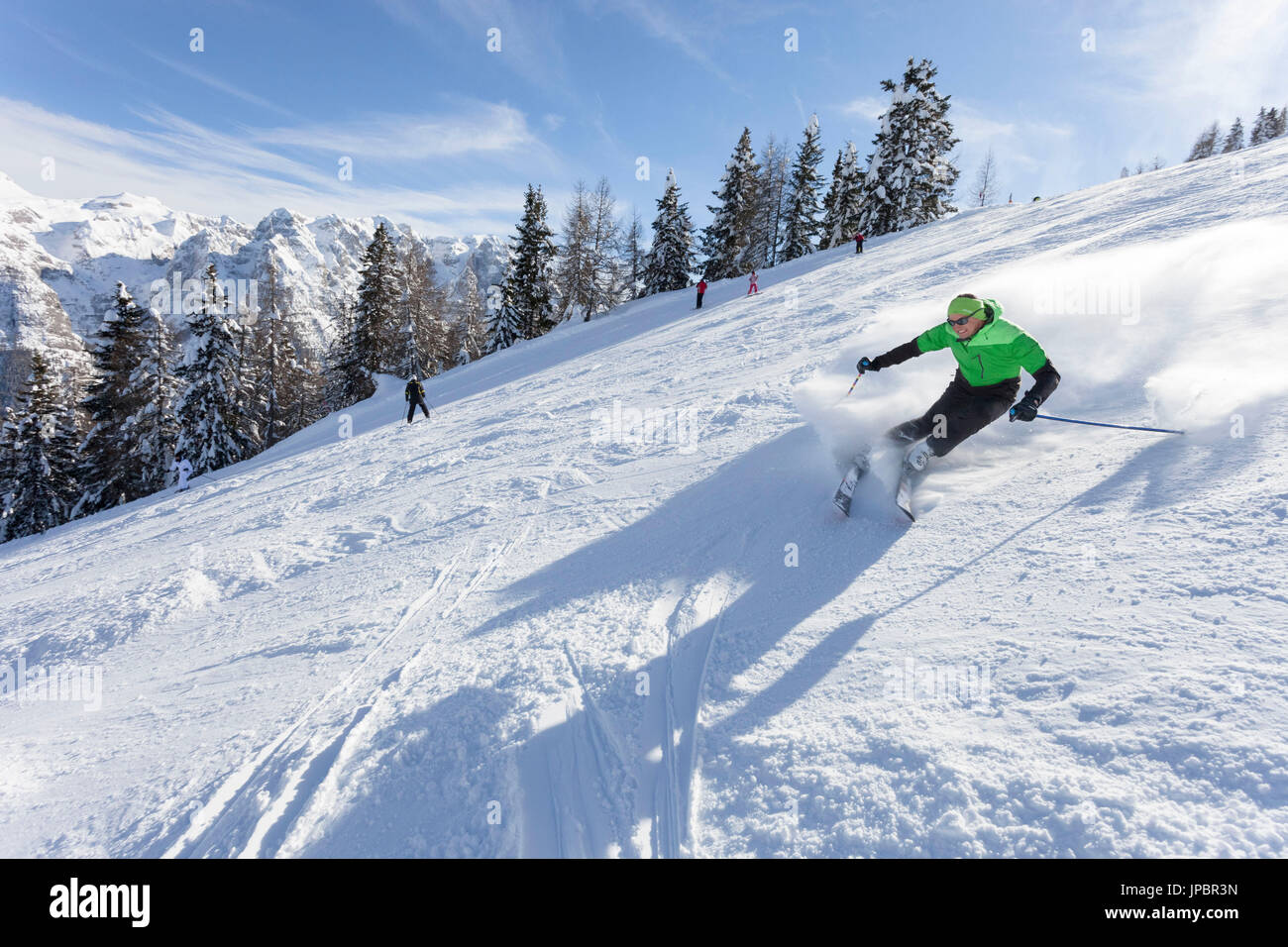 a skier is skiing along the slopes in the Folgarida ski resort with Brenta Group in the background Stock Photo