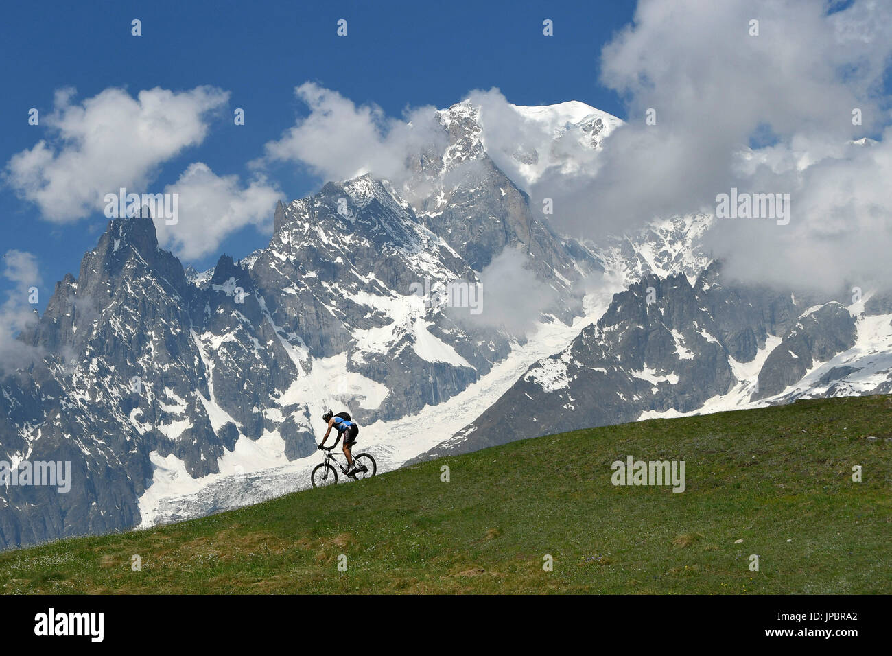 MTB Biker with Monte Bianco (mont Blanc) on background,Val Ferret, Aosta Valley,Italy - Stock Image