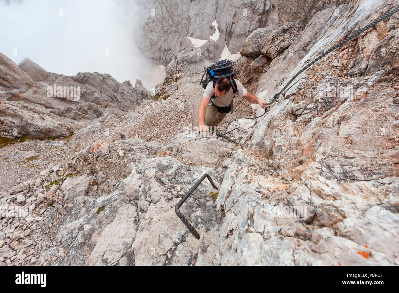 Hikers on the itinerary of the visit to the monumental zone of Punta Serauta, Marmolada. The path running between caves and trenches. Dolomites - Stock Image