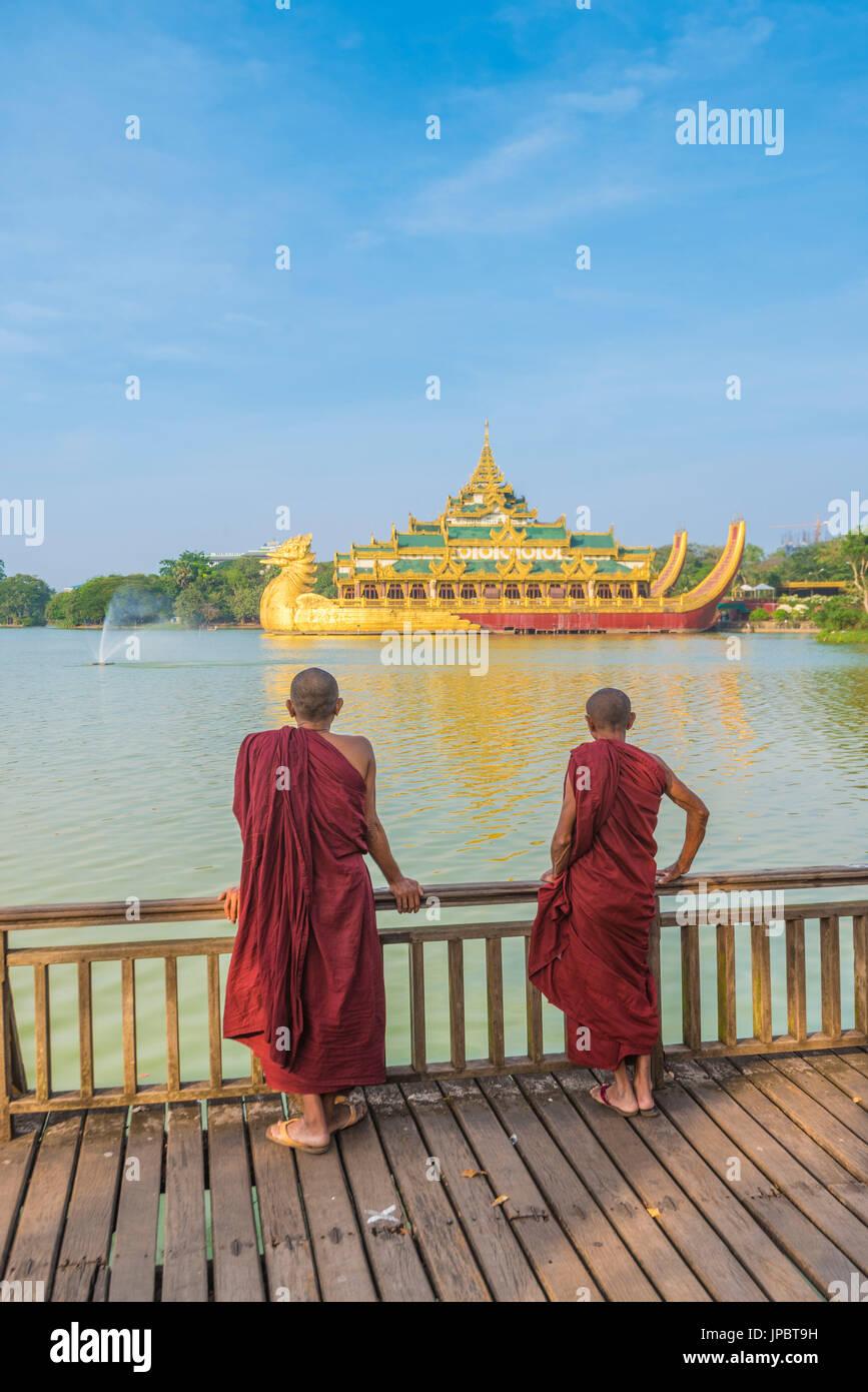 Yangon, Myanmar (Burma). Two monks watching the Karaweik Palace on the Kandawgyi Lake. Stock Photo