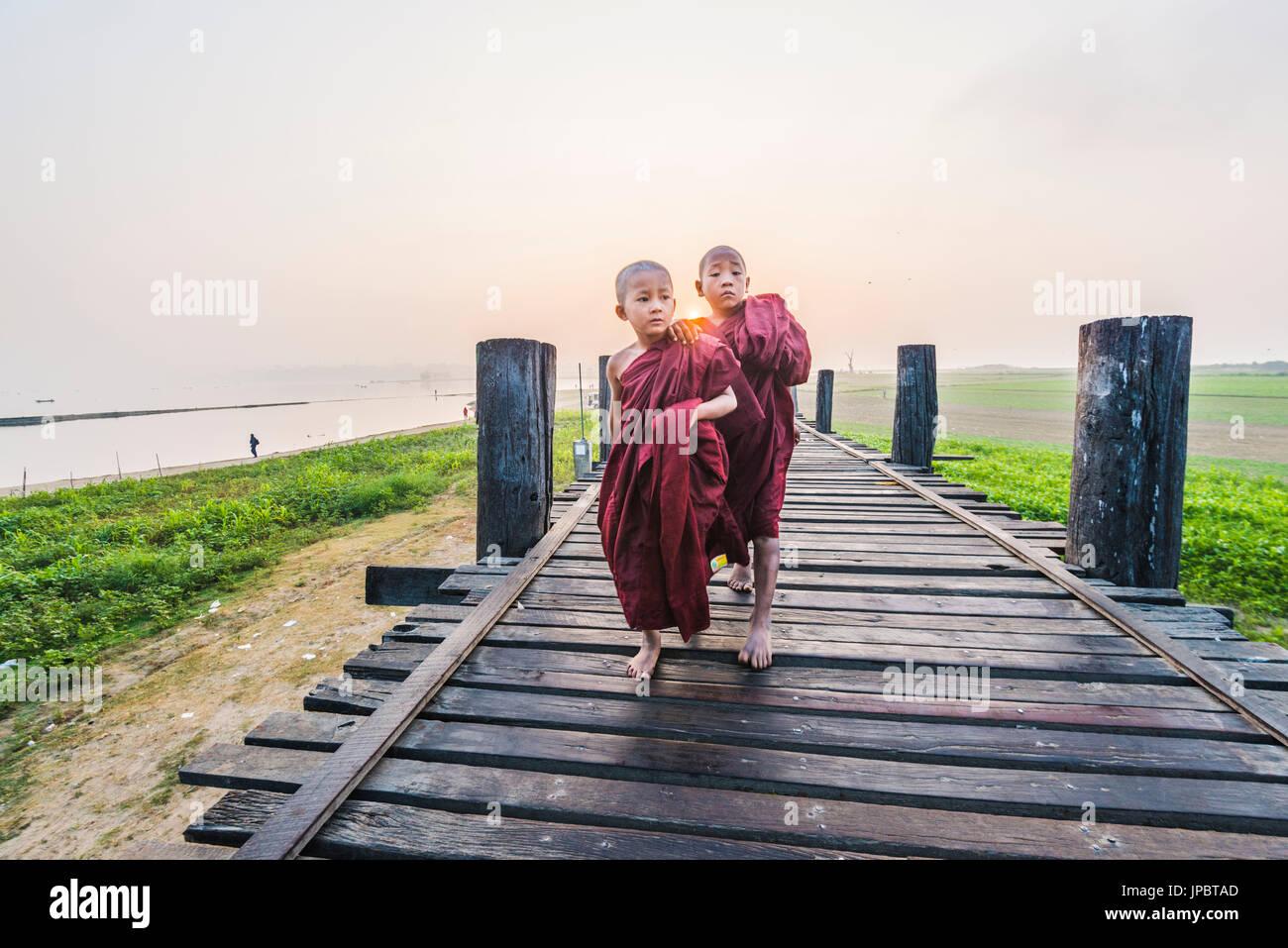 Amarapura, Mandalay region, Myanmar. Monks walking on the U Bein bridge at sunrise. - Stock Image
