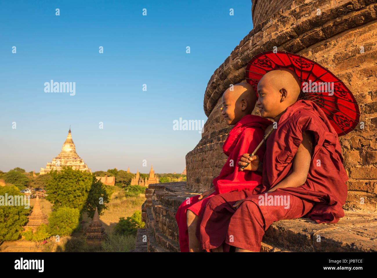 Bagan, Mandalay region, Myanmar (Burma). Two young monks sitting on top of a stupa with the Shwesandaw pagoda in Stock Photo