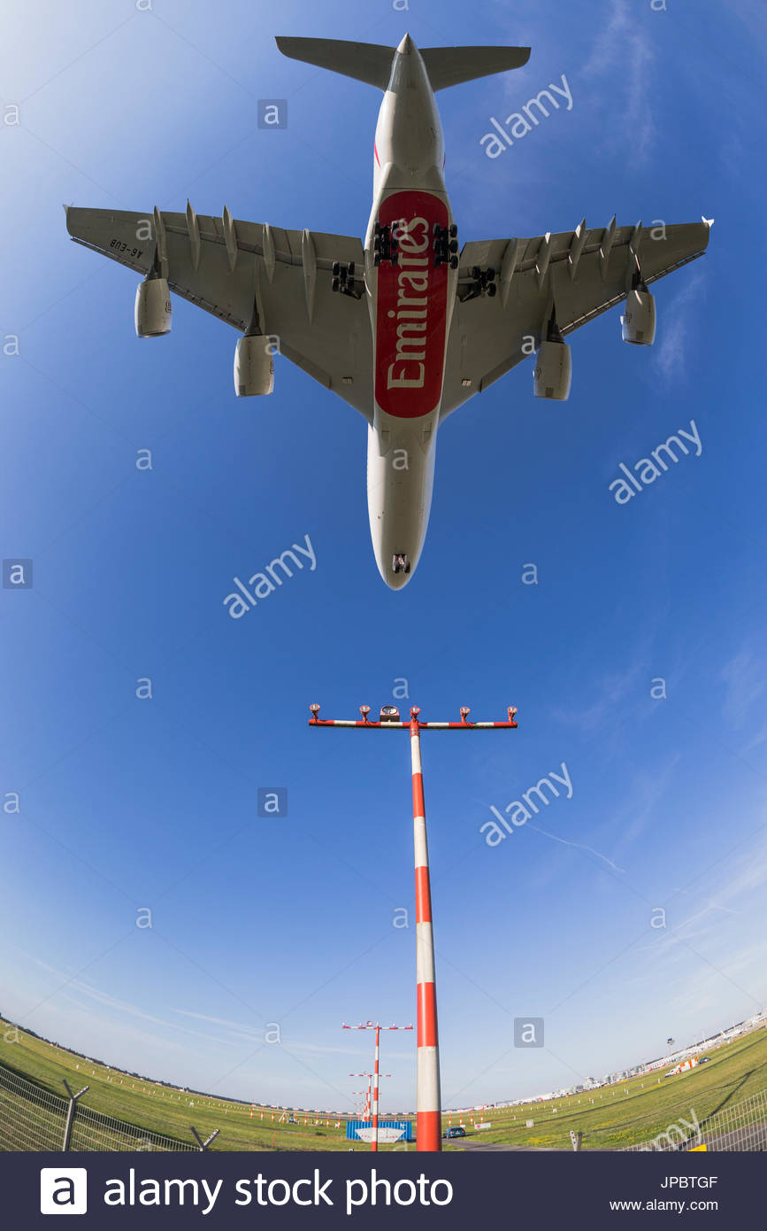 Airbus A380 landing at Dusseldorf airport long-haul jet final runway approach low flying overhead runway landing light mast guide beam antennae - Stock Image