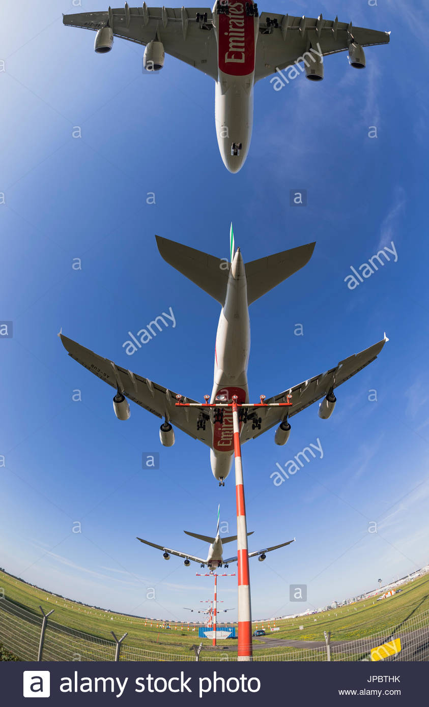 Airbus A380 landing at Dusseldorf airport various stages before touchdown final runway approach long-haul jet flying low overhead landing light mast - Stock Image