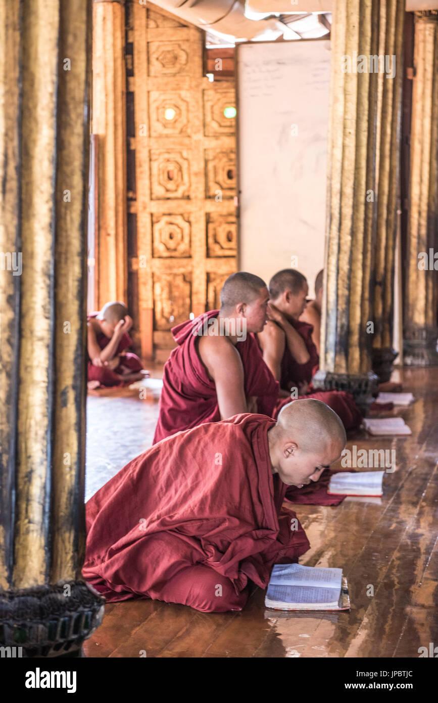 Nyaungshwe, Inle lake, Shan State, Myanmar.  Novice monks praying at the Shwe Yaunghwe Kyaung. - Stock Image