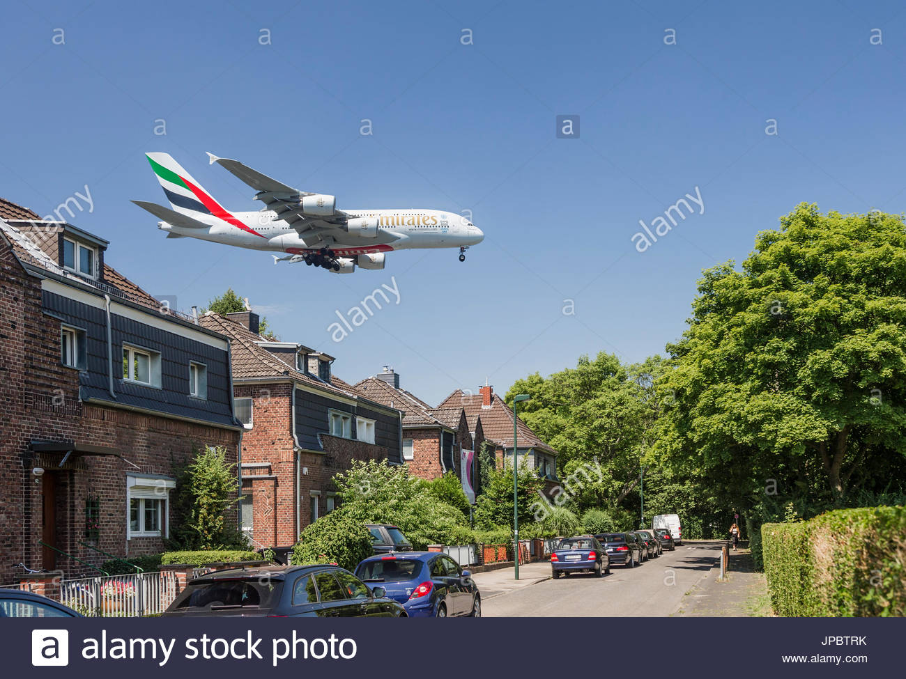 Airbus A380 over suburban residential area loud noise environment pollution housing buildings parking cars park - Stock Image