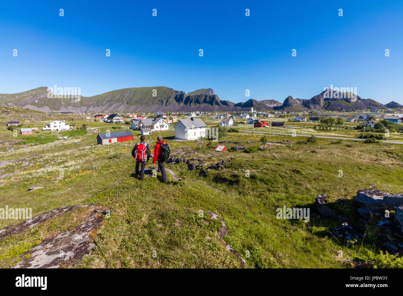 Hikers admire the village of Sorland surrounded by green meadows Vaeroy Island Nordland county Lofoten archipelago Norway Europe - Stock Image