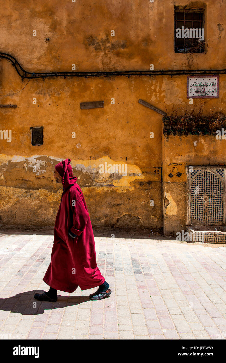 Fes, Marocco, North Africa. Passerby through the streets wearing a traditional dress. - Stock Image