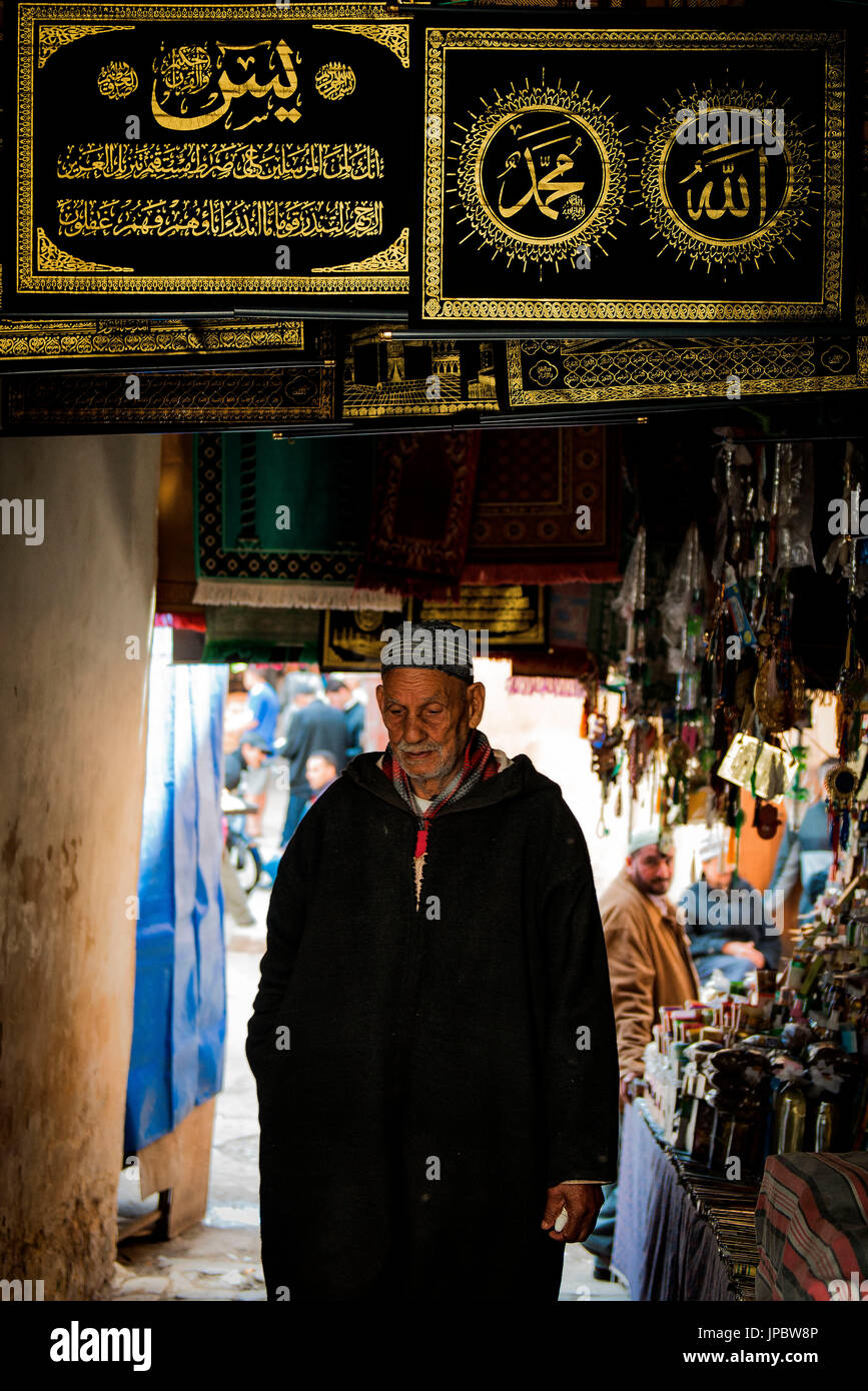 Fes, Marocco, North Africa. Elderly passerby through the streets wearing a traditional moroccan dress. - Stock Image