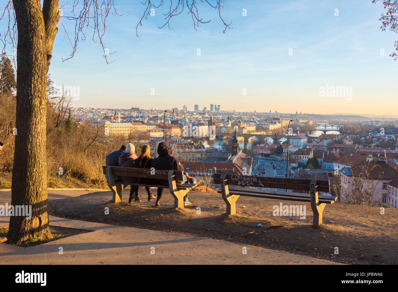 People on a bench admire the historical buildings  and bridges on Vltava (Moldava) river at sunset Prague Czech Stock Photo