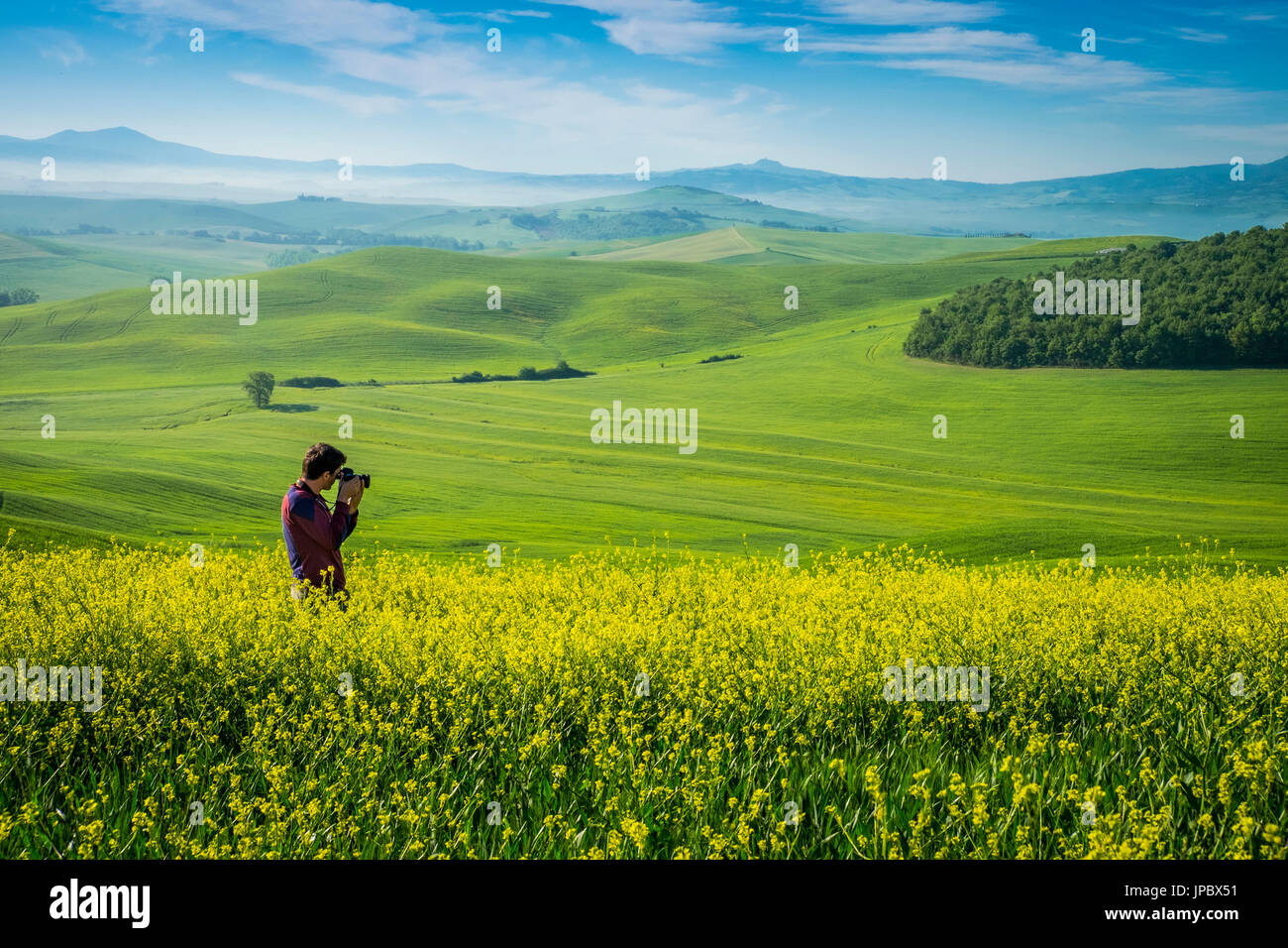 Orcia Valley, Siena district, Tuscany, Italy, Europe. Man takes pictures in a rapessed expanse. - Stock Image